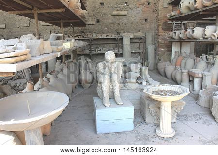 Plaster casts of victim of eruption Mount Vesuvius and ancient pottery in Pompeii - ancient Roman city in Italy. Pompeian excavations.