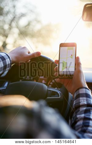 Man in plaid shirt sitting in the car and holding black mobile phone with map gps navigation toned at sunset.