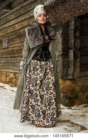 girl in national Russian style in a gray fur coat and a lacy dress costs near a wooden lodge in the winter