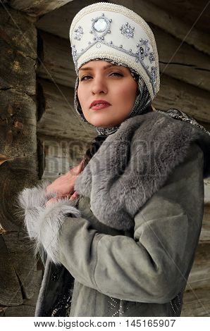 girl's portrait in old Russian style in a gray fur coat with a traditional headdress
