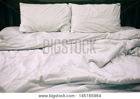 Messy white bed and pillow in the morning