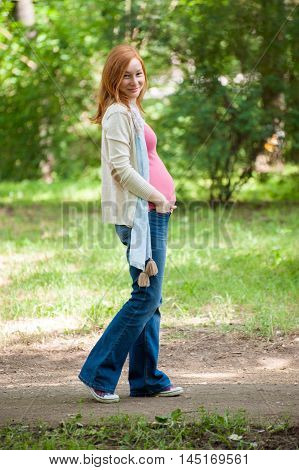 Outdoor portrait of a pregnant redhead woman