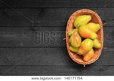 Close up view of ripe pears in a basket on wooden background. View with fresh pears. Ripe pears background. Free place for text.Top view