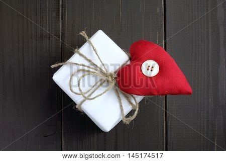 holiday gift decorated with a warm heart with a button standing on a wooden background top view / heartfelt congratulation with a love