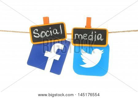 Kiev Ukraine - August 02 2016: Facebook and Twitter logos printed on paper hangind on a rope with tag orange clothespins with chalk written words