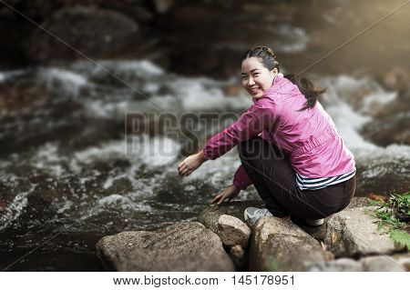 Vacation lifestyle scene of woman wearing sport cloths sitting beside canal in morning time. Woman activity on holiday concept.