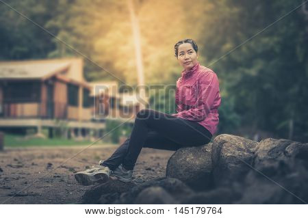 Vacation lifestyle scene of woman wearing sport cloths sitting in park and enjoy with nature in morning time. Woman activity on holiday concept with vintage filter effect