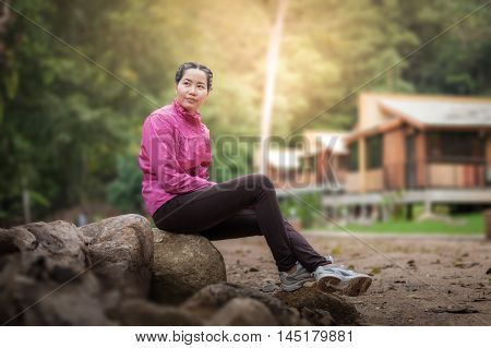Vacation lifestyle scene of woman wearing sport cloths sitting in park and enjoy with nature in morning time. Woman activity on holiday concept.