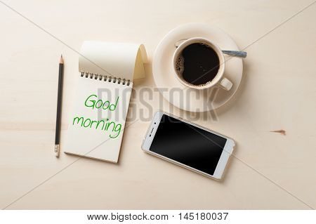 """Good morning"" is written on opened notebook with blank area pen smart phone and coffee cup on wood table in morning time"