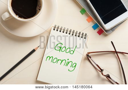 """Good morning"" is written on opened notebook with blank area and pencil on wood table with coffee cup smartphone and glasses beside in morning time"