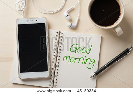 """""""Good morning"""" is written on opened notebook with blank area pen smart phone and coffee cup on wood table in morning time"""