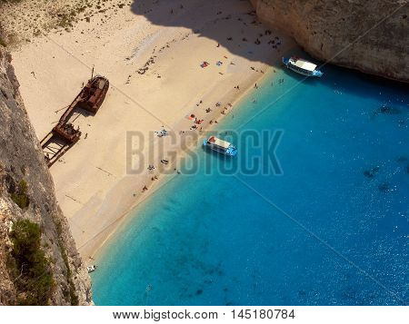 Top view at island Zakynthos attraction Navagio beach with boats and tourists
