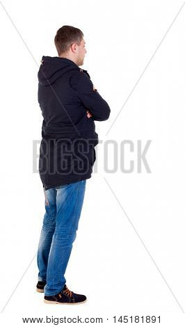 Back view of handsome man in winter jacket looking up. Standing young guy in parka. Man in warm jacket is left side with his arms crossed.