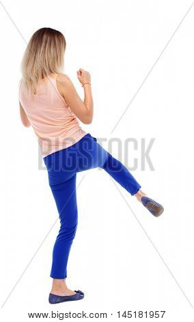 back view of standing girl pulling a rope from the top or cling to something. Isolated over white background. The blonde in a pink shirt swung his foot.
