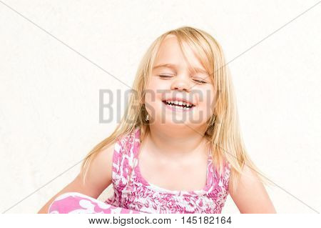 Closeup Portrait of Beautiful Laughing Toddler Girl Eyes Closed Neutral Background