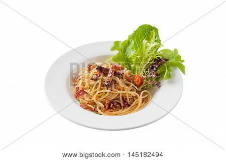Front view of Thai Japanese and European fusion food style spicy pasta with bacon and dried chili in ceramic dish isolated on white background