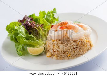 Thai style cuisine fried rice with shrimp garnished with vegetables in ceramic dish