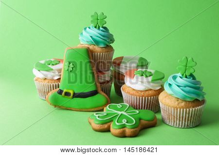 Cupcakes and cookies on green background. Saint Patrics Day concept