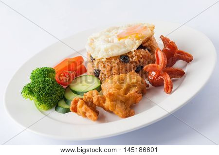 Thai style cuisine fried rice with raisin deep fried chicken sausage and fried egg garnished with vegetables in ceramic dish