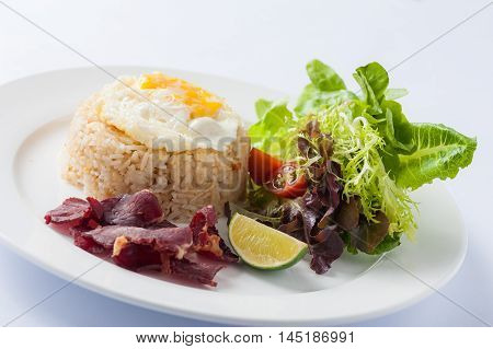 Modern Thai style fried rice with salted beef and fried egg in ceramic dish