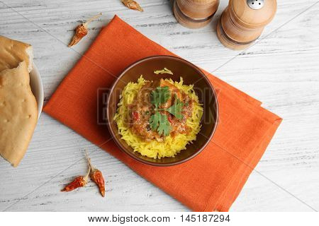 Tasty dinner with chicken curry and rice in bowl on napkin