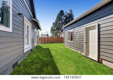 Blue Siding House With Matching Detached Garage