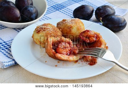 Plum dumplings filled with juicy cinnamon sugar inside the plums covered with roasted breadcrumbs.