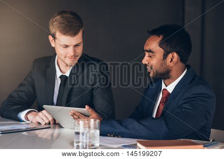 Two young businessmen in suits talking together over a digital tablet while sitting at a table in a modern boardroom