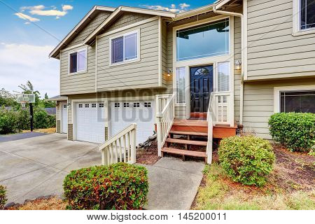 Exterior Of Two Story Clapboard Siding House With Three Garage Spaces