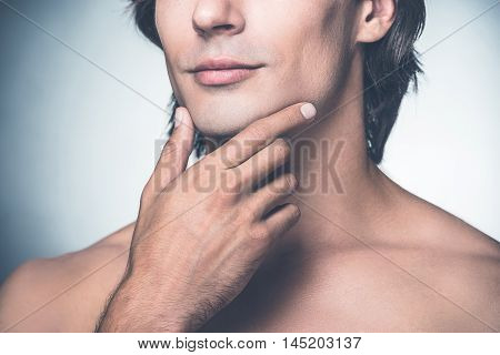 Feeling clean and fresh. Close-up of handsome young shirtless man holding hand on chin while standing against grey background