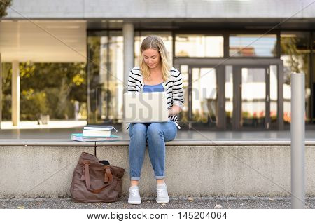 Young Female Student Sitting Outside Using Laptop