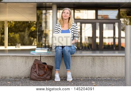 Daydreaming Student Sitting Outside Using Laptop