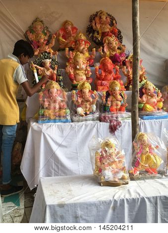 A vendor arranging colorful Ganesha Idols in his makeshift shop on the street. Ganesh festival is the popular religious event in India. September 1, 2016. Nagpur, Maharashtra.