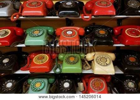 Collection of vintage rotary phone arrange on the shelve