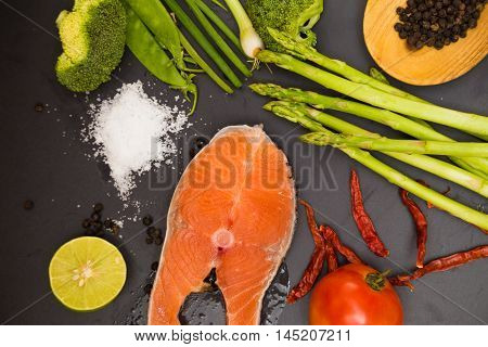 Fresh Raw Salmon Filet With Spicy Herbs On Black Plate