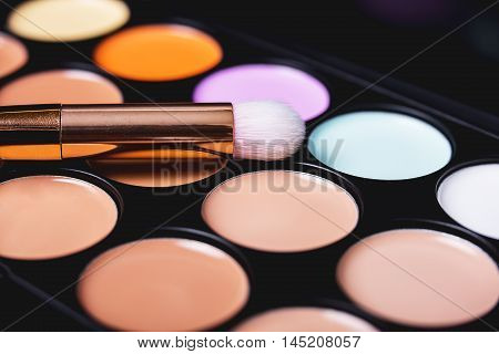 Palette concealer and correctors. Make-up base. Isolated on black background