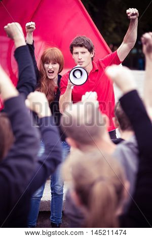 Young activists shouting slogans through a megaphone during a rally
