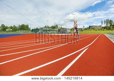 Full length of fit woman running on sports tracks