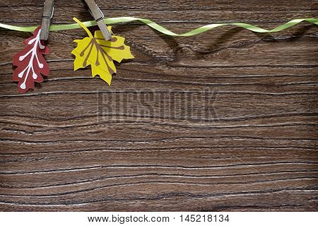 Autumn colored paper leaves on a wooden board copy space. A sheet of paper craft for children. Children's art project.