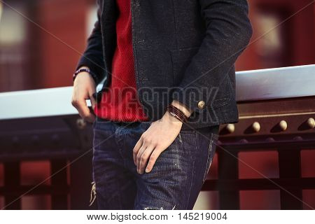 Men`s casual street style clothes with jeans jacket red pullover and wristband