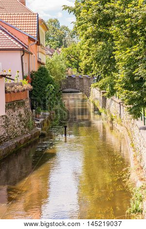 Vertical photo of small stream which is running through a small town in a channel built from stones. Old wall is on one side with trees and few houses are on second side.