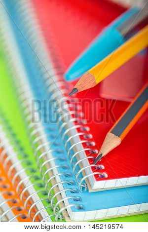 Closeup shot of pensil against defocused notebooks in background. Focus on the tip of grey pencil.