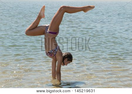 Happy young woman doing cartwheel on the beach bikini
