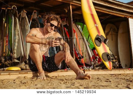 Young handsome surfer man in eyeglasses sitting and using smartphone outdoors