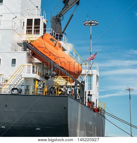orange free-fall life boat for emergency crew evacuation installed on cargo ship