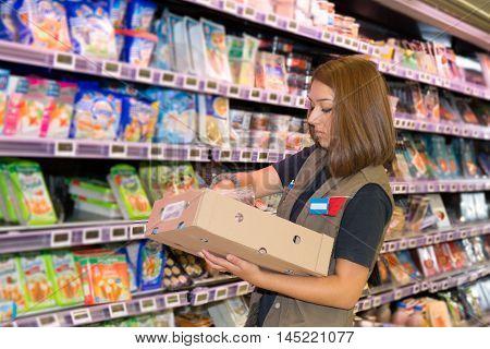 Brunette worker taking a products in shelf in supermarket