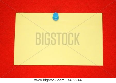 A Yellow Note Held On A Red Felt Notice Board.