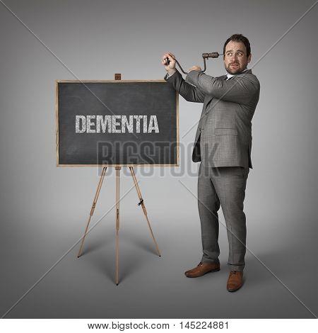 Dementia text on blackboard with businessman drilling his head
