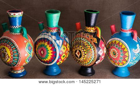 Still life of four decorated colorful handcrafted pottery jugs on sackcloth background one of the art works of Ebtessam ElGohary a contemporary Egyptian artist specialized in pottery painting art