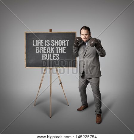 Life is short break the rules text on  blackboard with businessman wearing boxing gloves